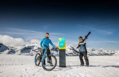 Herr lädt sein E-Bike an der Ladestation am Berg auf, Dame trägt die Schi auf den Schultern